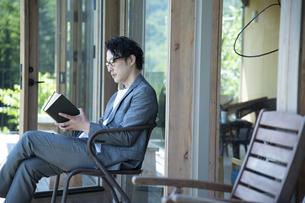 バルコニーで読書をするビジネスマンの写真素材 [FYI04604085]
