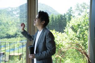 外を眺めるビジネスマンの写真素材 [FYI04604170]