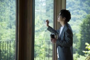 外を眺めるビジネスマンの写真素材 [FYI04604172]