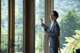外を眺めるビジネスマンの写真素材 [FYI04604173]