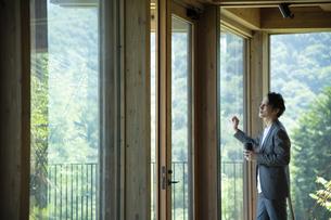 外を眺めるビジネスマンの写真素材 [FYI04604176]