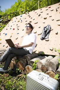 クライミングウォールの前で仕事をするビジネスマンの写真素材 [FYI04604182]