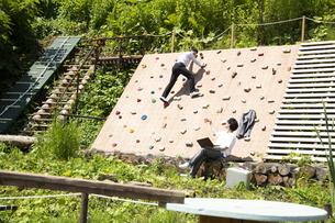 クライミングウォールの前で仕事をするビジネスマンとボルダリングを楽しむビジネスマンの写真素材 [FYI04604186]