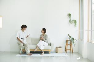 室内でソファに座りスマホを見る若い女性と男性の写真素材 [FYI04604362]