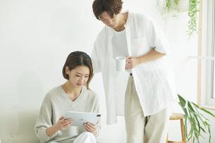 室内でソファに座りタブレットPCを見る若い女性と男性の写真素材 [FYI04604363]