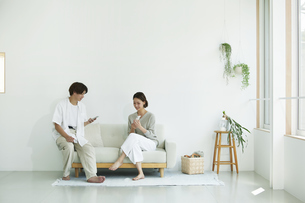 室内でソファに座りスマホを見る若い女性と男性の写真素材 [FYI04604369]