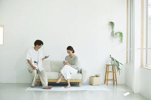 室内でソファに座りスマホを見る若い女性と男性の写真素材 [FYI04604378]