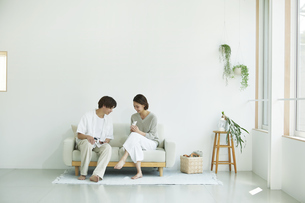 室内でソファに座りスマホを見る若い女性と男性の写真素材 [FYI04604386]