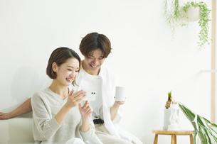 室内でソファに座りスマホを見る若い女性と男性の写真素材 [FYI04604398]