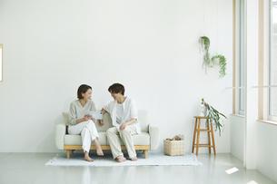 室内でソファに座りタブレットPCを見る若い女性と男性の写真素材 [FYI04604419]