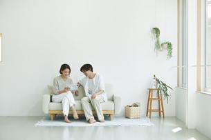 室内でソファに座りタブレットPCを見る若い女性と男性の写真素材 [FYI04604421]