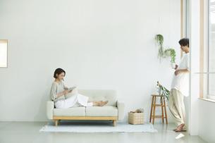 室内でソファに座りタブレットPCを見る若い女性と男性の写真素材 [FYI04604436]