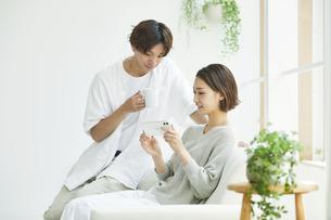 室内でソファに座りスマホを見る若い女性と男性の写真素材 [FYI04604437]