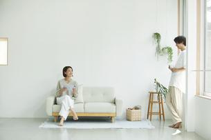 室内でソファに座りタブレットPCを見る若い女性と男性の写真素材 [FYI04604442]