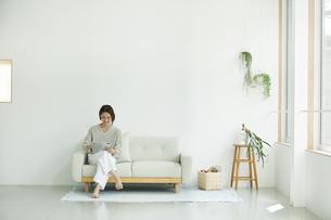 室内でソファに座りタブレットPCを見る若い女性の写真素材 [FYI04604444]