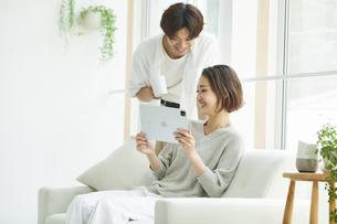 室内でソファに座りタブレットPCを見る若い女性と男性の写真素材 [FYI04604706]