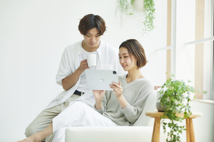 室内でソファに座りタブレットPCを見る若い女性と男性の写真素材 [FYI04604712]
