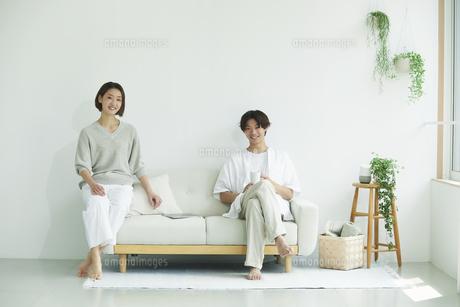 室内でソファに座るカメラ目線の若い女性と男性のポートレートの写真素材 [FYI04604714]