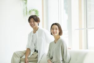 室内でソファに座るカメラ目線の若い女性と男性のポートレート の写真素材 [FYI04604717]