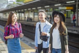 駅ホームで電車を待つ女子旅をする女性3人の写真素材 [FYI04604780]