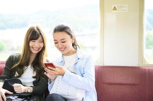 電車で女子旅をする女性2人の写真素材 [FYI04604806]