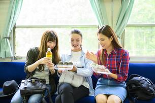 電車でお弁当を食べる女子旅をする女性3人の写真素材 [FYI04604814]