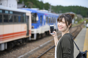 電車を待つ女子旅をする女性の写真素材 [FYI04604928]