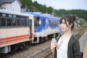 電車を待つ女子旅をする女性の写真素材 [FYI04604929]
