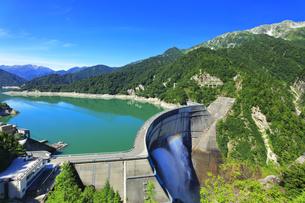 夏の立山 黒部ダムに船の航跡と観光放水に虹の写真素材 [FYI04604987]