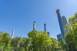 セントラルパークに生い茂る新緑の木々の後ろにそびえ立つミッドタウンマンハッタンの摩天楼。の写真素材 [FYI04606175]