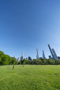 新緑が生い茂るセントラルパークの芝生の広場 シープメドウで寛ぐ人々とミッドタウンマンハッタンの摩天楼の写真素材 [FYI04606190]