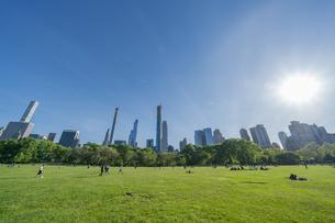 新緑が生い茂るセントラルパークの芝生の広場 シープメドウで寛ぐ人々とミッドタウンマンハッタンの摩天楼の写真素材 [FYI04606191]