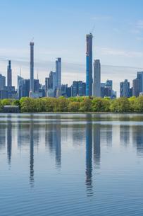 セントラルパークの貯水池に映り込む生い茂る新緑の木々とミッドタウンマンハッタンの摩天楼の写真素材 [FYI04606221]