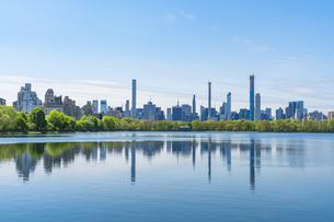 セントラルパークの貯水池に映り込む生い茂る新緑の木々とミッドタウンマンハッタンの摩天楼の写真素材 [FYI04606228]