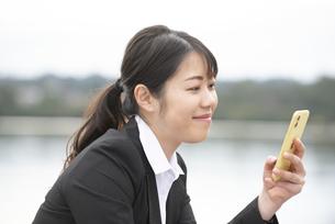 スマホを持って微笑んでいるスーツ姿の女性の写真素材 [FYI04606275]
