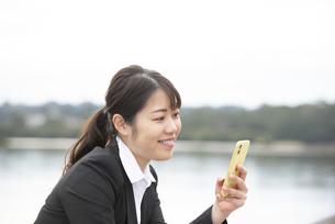 スマホを持って微笑んでいるスーツ姿の女性の写真素材 [FYI04606276]