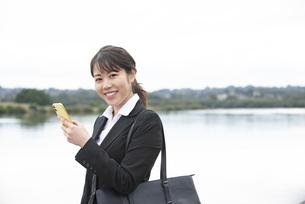 スマホを持って笑っているスーツ姿の女性の写真素材 [FYI04606277]