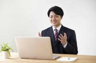 パソコンでオンライン面接をする男子の就活生の写真素材 [FYI04606335]