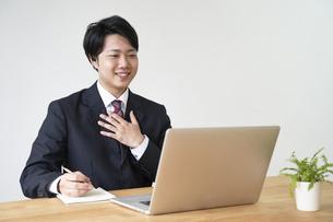 パソコンでオンライン面接をする男子の就活生の写真素材 [FYI04606342]