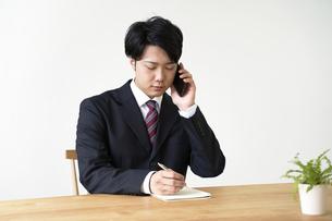 電話をしながらメモを書き留める男子の就活生の写真素材 [FYI04606344]