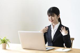 パソコンでオンライン面接をする女子の就活生の写真素材 [FYI04606353]