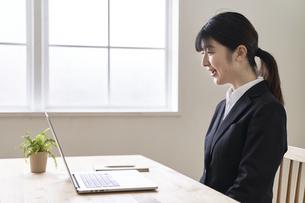 パソコンでオンライン面接をする女子の就活生の写真素材 [FYI04606359]