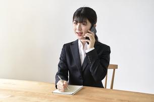 電話をしながらメモを書き留める女子の就活生の写真素材 [FYI04606365]