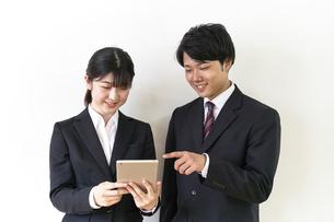 iPadを操作するスーツ姿の男女の学生の写真素材 [FYI04606367]