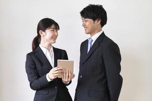 スーツ姿でiPadを持った女子学生と見つめ合う男子学生の写真素材 [FYI04606369]