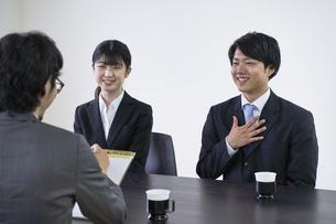 集団面接で面接官と会話をする男子の就活生の写真素材 [FYI04606409]