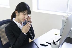 緊張しながら電話対応をする新入社員の女子の写真素材 [FYI04606412]