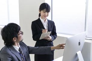 上司に仕事を教えてもらいメモを書き留める新入社員の女子の写真素材 [FYI04606417]