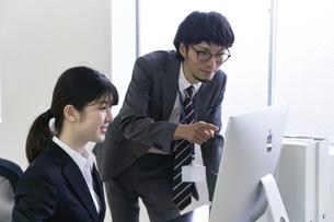 上司に仕事を教えてもらいパソコンを操作する新入社員の女子の写真素材 [FYI04606419]