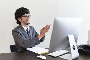 パソコンでのオンライン面接を行い拍手する男性の面接官の写真素材 [FYI04606422]